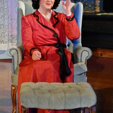 Carrie Kincaid as Ruth sitting in chair in a red dress