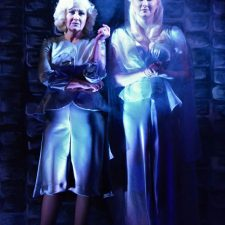 Elvira and Ruth standing in dim blue light with fog behind them