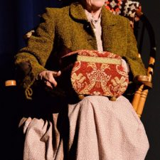 Ginny Racette sitting in a rocking chair acting in On Golden Pond