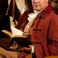 Joe-Michael Jackson in costume reading a book while acting in 1776